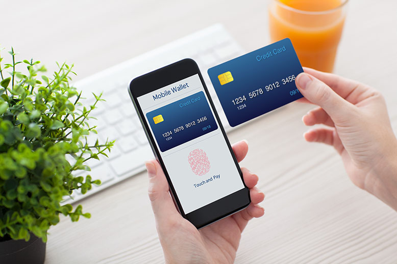 Photo of a person holding an iPhone and credit card getting ready to complete an online payment with Apple Pay.